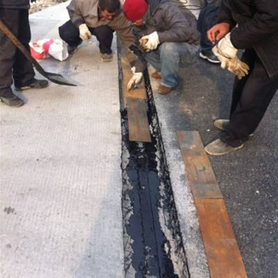 Workers are placing the steel plates on the asphaltic plug joint material.